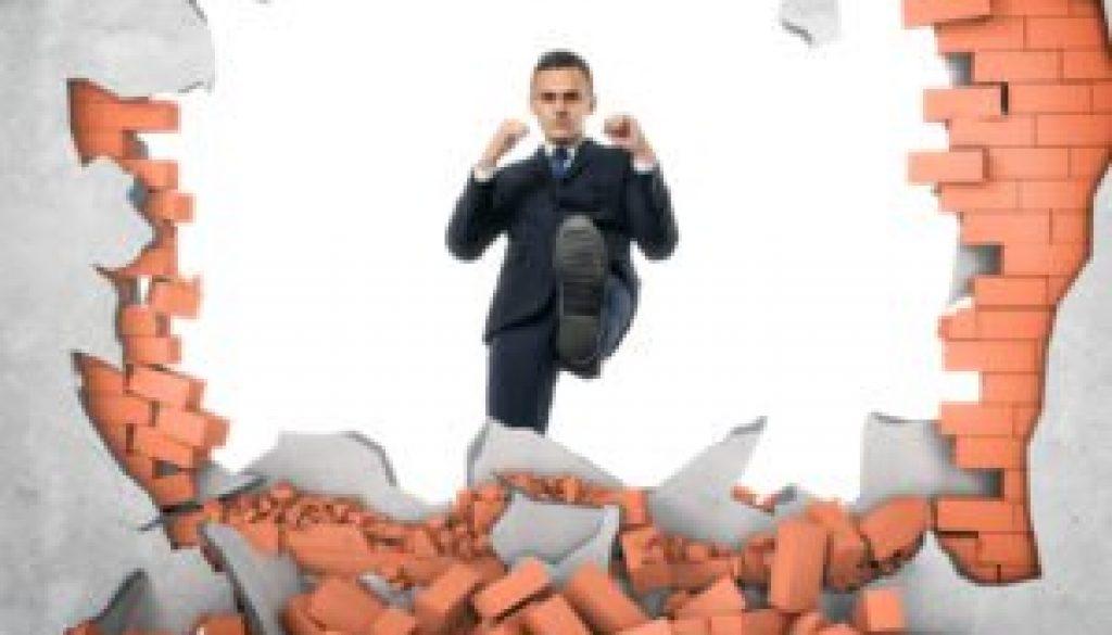 businessman-kicks-through-brick-wall-300x235.jpg